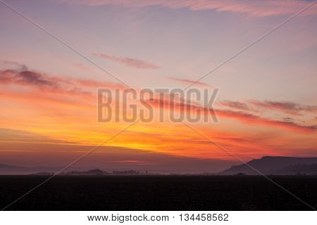 beautiful scene of late sunset with red skies over darken ground and some silhouettes of trees and hills in the far background