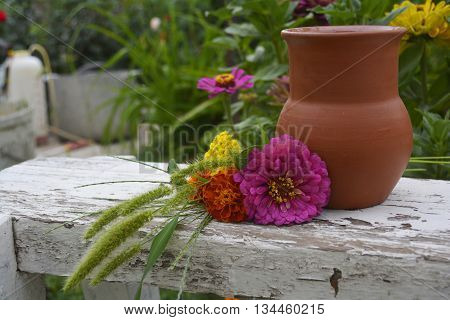 clay vase and wild flowers in the garden, rustic still life