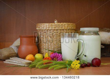 milk, fruit, bread, wildflowers, clay and wicker ware-rural still life