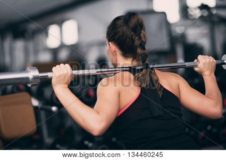 Young Woman Exercising In Gym With Olmipic Barbell