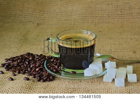 The photo shows a glass cup on a saucer filled to the full brown coffee. Cup is standing on a substrate made of raw, coarse fabric. A cup are scattered coffee beans and sugar cubes.