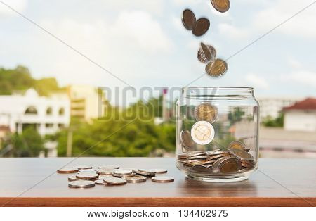 Close up of glass bottle stacking silver coins falling on wooden table Business finance and money concept Save money for prepare in the future Vintage style