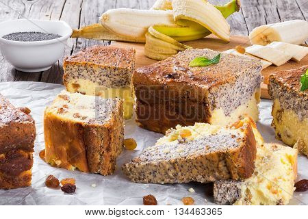 homemade banana cheesecake with poppy seeds on a parchment paper on an old wooden table with pieces of banana and raisins close-up