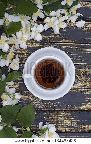 cup of jasmine tea with jasmine flowers on a table
