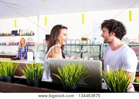A beautiful young couple sitting and chating in a coffee shop