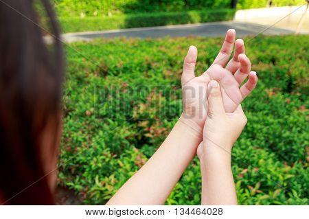 Asian woman hands pain in garden concept