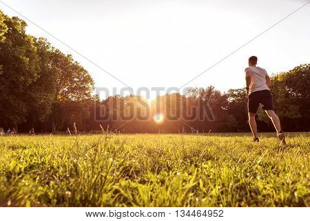 A handsome young man doing sports in the sunset in a park.