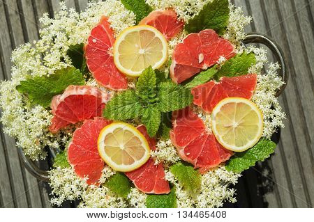 Elderberry flower lemon balm leaves and red grapefruit slices in a bowl on a wooden table