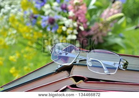 Reading glasses with a stack of inverted open books on the background of bouquet of wildflowers and green grass