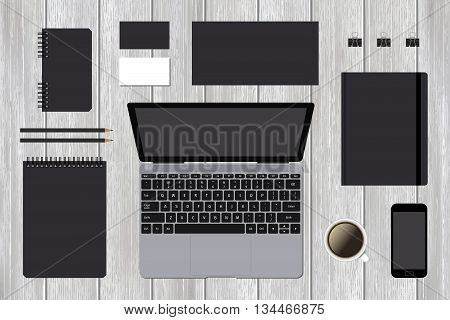 Mock-up stationery business template with laptop and smartphone on wooden background. Blank stationery for your design.