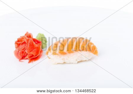 Traditional salmon nigiri sushi with wasabi and ginger. Macro. Photo can be used as a whole background.