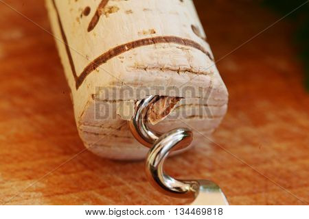 Corkscrew with wine cork background on table