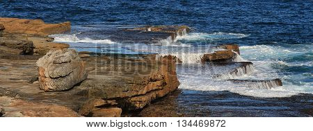 Pacific water flowing over rocks. Scene at Maroubra Beach Sydney.