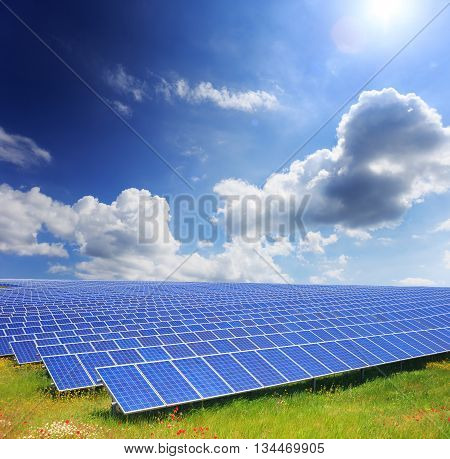 Solar panels with green field and clody sky