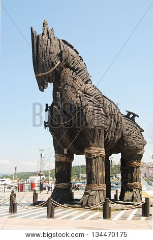 Canakkale, Turkey - July 20, 2013. Trojan Horse from the movie Troy on the waterfront promenade of Canakkale, with people and city scenery in the background.