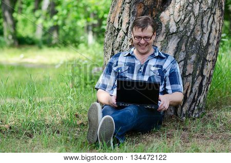 Man with laptop is resting in pine forest near large trunk of old pine tree in sunny summer day
