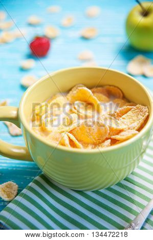 cornflakes with milk strawberry apple on blue wooden table in bowl closeup