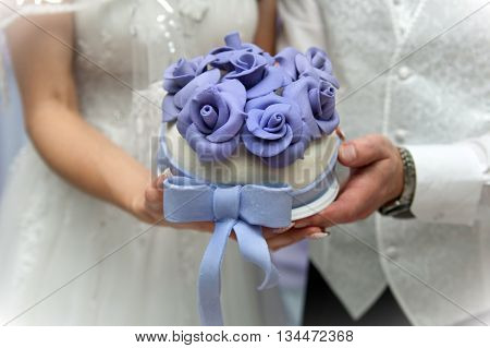 wedding cake in the hands of the newlyweds