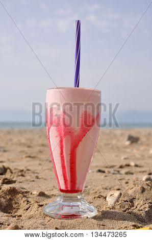 Strawberry milk shake on a summer beach