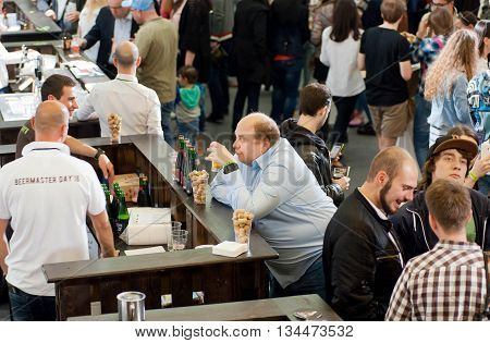 KYIV, UKRAINE - MAY 21, 2016: Lonely man drinking beer in crowd of people during Beermaster Day Festival on May 21, 2016. Kiev is the 8th most populous city in Europe.