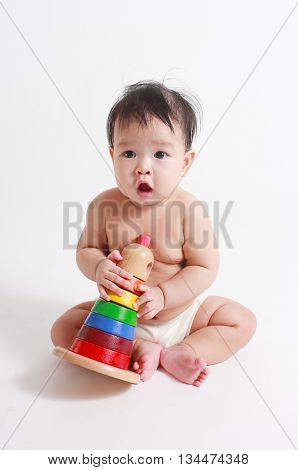 Cute baby playing with colorful toy pyramid isolated on white.