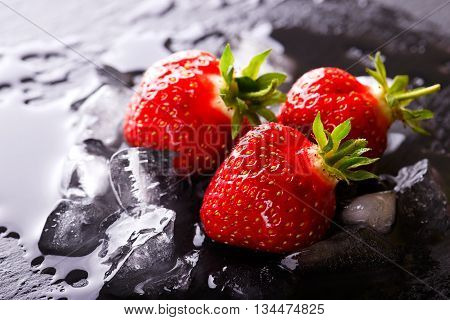 Three Fresh Red Strawberries On Slate Stone With Ice