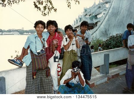 RANGOON / MYANMAR - CIRCA 1987: A group of professional photographers pose for a photograph with their cameras at the entrance to the Karaweik Palace Restaurant in Rangoon.