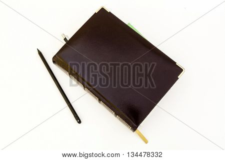Dark brown leather notebook-business diary and black pencil.