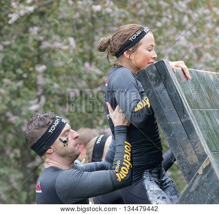STOCKHOLM SWEDEN - MAY 14 2016: Man helping a women climbing over a plank obstacle in the obstacle race Tough Viking Event in Sweden May 14 2016