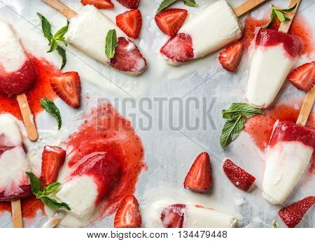 Strawberry yogurt ice cream popsicles with mint over steel tray background. Top view, copy space. Food frame