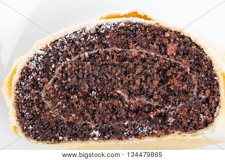 Delicious poppy seed roll covered with sugar powder. Macro. Photo can be used as a whole background.