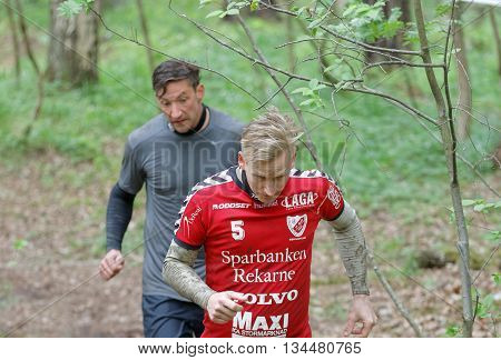 STOCKHOLM SWEDEN - MAY 14 2016: Two men running in the forest ducking to avoid a branch in the obstacle race Tough Viking Event in Sweden May 14 2016