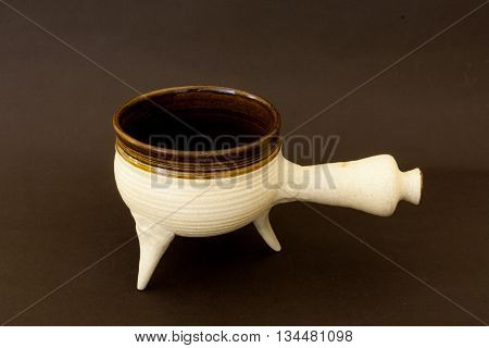 Ceramic pan with handle and three legs. Inside covered with clay glaze. Based on medieval pots.