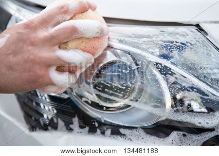 Handle Carwash Concept - Man Washing Car Headlamp With Sponge And Foam