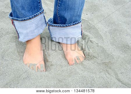 Female wearing cuffed blue jeans with her feet buried in sand. Close-up on feet.