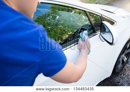 Back View Of Young Man Cleaning Car With Microfiber Cloth