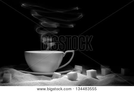 White tea cup and sugar on a black background
