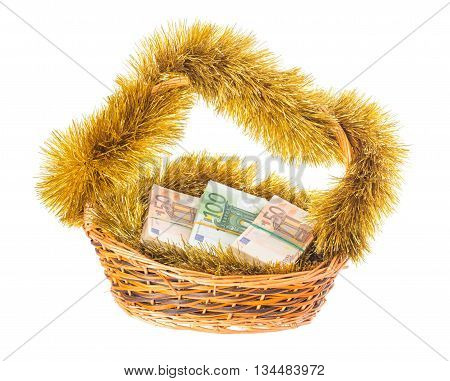 Wicker basket full of euro bills with christmas golden tinsel. Isolated on a white background.