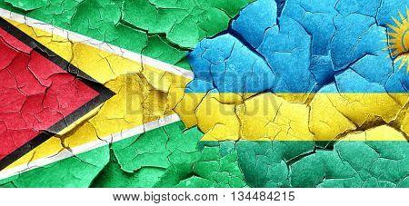 Guyana flag with rwanda flag on a grunge cracked wall