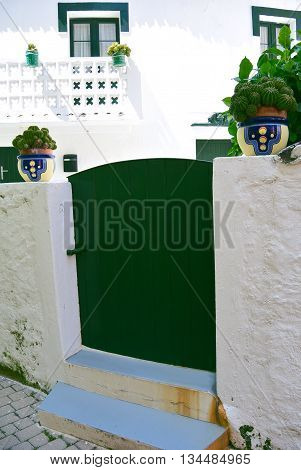Beautiful white wall with green windows in Galicia, Spain.