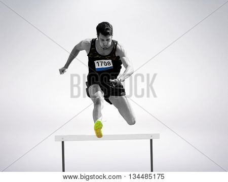 Sportsman practising hurdles against grey background