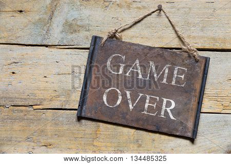 Rusty Metal Sign On Wooden Table, Text Game Over