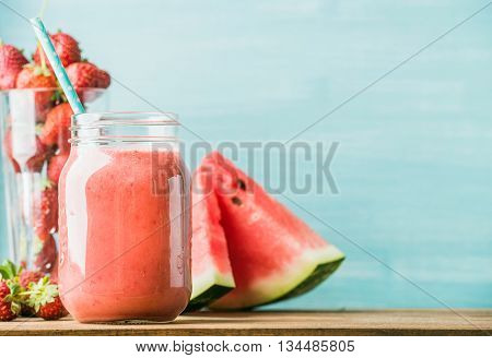 Freshly blended red fruit smoothie in glass jar with straw. Turquoise blue background, copy space