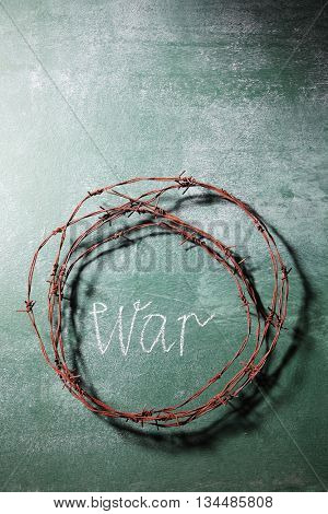 barbwire on top of blackboard with text war