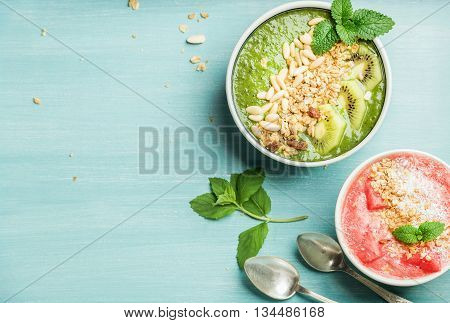 Healthy summer breakfast concept. Colorful fruit smoothie bowls with nuts and oat granola on turquoise blue background . Red and green, top view, copy space