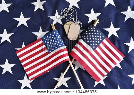 Top view of two crossed American Flags on the star field of a large flag with military dog tags. Perfect for Veterans Day, Memorial Day or other patriotic projects.