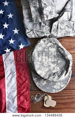 Top view of military fatigues, dog tags and American Flag on a wood background. Military service concept for Memorial Day, Veterans Day and Patriotic events.