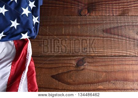 Closeup of an American flag on a dark wood table with copy space.