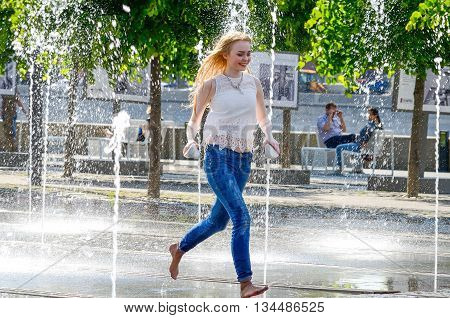 MOSCOW, RUSSIA - May 26, 2016: Unknown young beautiful woman bathes in city fountain. Hot summer heat. Girls in wet jeans. Icy freshness, happiness.