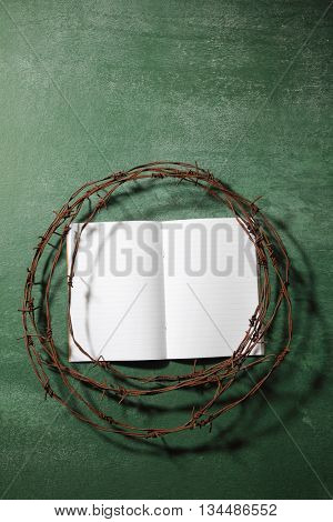 work book surround by barbwire
